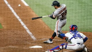 Mike Tauchman #29 of the San Francisco Giants hits a grand slam home run against the Texas Rangers in the top of the eighth inning at Globe Life Field on June 8, 2021 in Arlington, Texas.