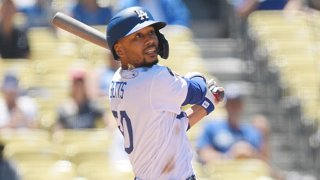 Mookie Betts #50 of the Los Angeles Dodgers hits a one run home run against Starting pitcher Dane Dunning #33 of the Texas Rangers during the third inning of their inter-league game at Dodger Stadium on June 13, 2021 in Los Angeles, California.