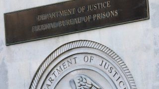 a sign for the Department of Justice Federal Bureau of Prisons is displayed at the Metropolitan Detention Center in the Brooklyn borough of New York