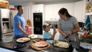 Chris and Kristen Umphlett prepare dinner with two of their four children, Kyria, 9, rear, and Derek 7, Wednesday, June 30, 2021, in their home in East Lansing, Mich. The Umphletts have fostered unaccompanied migrant children during the pandemic.
