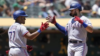 Texas Rangers' Joey Gallo, right, is congratulated by Andy Ibanez, left, after hitting a two-run home run during the fifth inning of a baseball game against the Oakland Athletics in Oakland, Calif., Thursday, July 1, 2021.