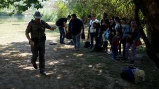 Texas Department of Public Safety officers work with a group of migrants who crossed the border and turned themselves in Del Rio, Texas