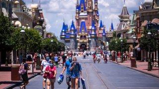 FILE - Guests on Main Street, U.S.A. in front of Cinderella Castle at Walt Disney World Resort's Magic Kingdom on Aug. 9, 2020, in Lake Buena Vista, Fla.