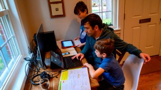 Joachim (R), 8, and Colin (L), 10, whose school was closed following the Coronavirus outbreak, do school exercises at home with their dad