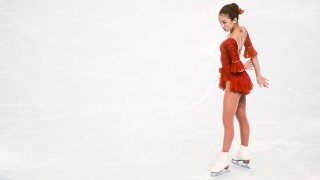 Michelle Kwan stands in her skates on the ice.