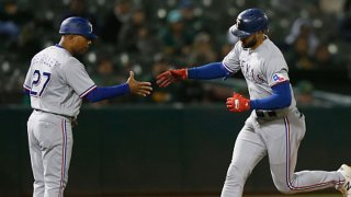 Joey Gallo #13 of the Texas Rangers celebrates with third base coach Tony Beasley #27 after hitting a solo home run in the top of the ninth inning against the Oakland Athletics at RingCentral Coliseum on June 30, 2021 in Oakland, California.
