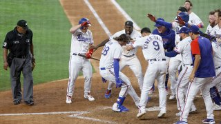 Jonah Heim #28 of the Texas Rangers celebrates with teammates after hitting a two -run walk-off home run to defeat Seattle Mariners 5-4 in ten innings at Globe Life Field on July 31, 2021 in Arlington, Texas.