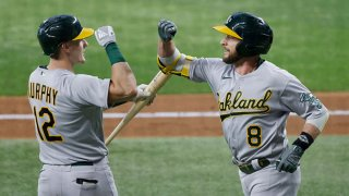 Jed Lowrie #8 of the Oakland Athletics celebrates with teammate Sean Murphy #12 after Lowrie hit a solo home run against the Texas Rangers during the fourth inning at Globe Life Field on July 10, 2021 in Arlington, Texas.
