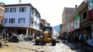 Workers clear the mud from a street in Bozkurt town of Kastamonu province, Turkey