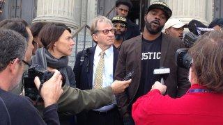 Robert Jones and defense attorneys with reporters