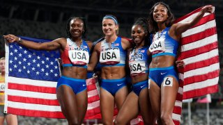 Team United States celebrates winning the silver medal in the final of the women's 4 x 100-meter relay at the 2020 Summer Olympics, Friday, Aug. 6, 2021, in Tokyo.
