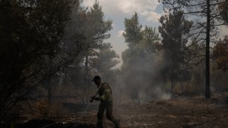 An Israeli firefighter works to extinguish a fire, on the second day of wildfires near Jerusalem, Monday, Aug. 16, 2021. Israel Fire and Rescue service said in a statement on Monday, that 45 firefighting teams accompanied by eight planes were working to contain five fires in the forested hills west of the city.