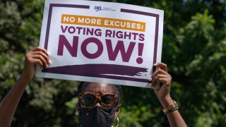 LaQuita Howard of Washington, with the League of Women Voters, attends a rally for voting rights, Tuesday, Aug. 24, 2021, near the White House in Washington.