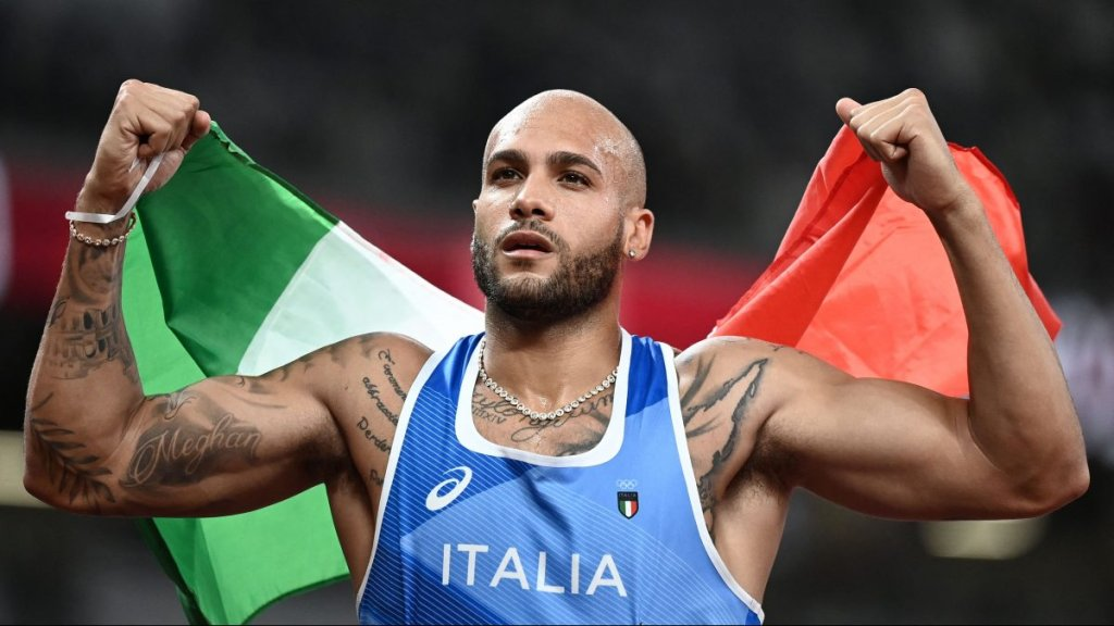 Italy's Lamont Jacobs holds his national as he celebrates winning the men's 100m final during the Tokyo 2020 Olympic Games at the Olympic Stadium in Tokyo on Aug. 1, 2021.