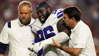 Defensive tackle Neville Gallimore #96 of the Dallas Cowboys is helped by trainers after an injury in the second half of the NFL preseason game against the Arizona Cardinals at State Farm Stadium on Aug. 13, 2021 in Glendale, Arizona.