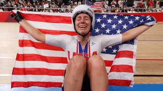 Jennifer Valente of Team United States celebrates winning the gold medal while holding the flag of her country during the Women's Omnium points race, 4 round of 4 of the track cycling on day sixteen of the Tokyo 2020 Olympic Games