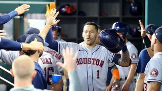 Carlos Correa #1 of the Houston Astros is greeted in the dugout in the third inning after a solo home run against the Texas Rangers at Globe Life Field on Aug. 28, 2021 in Arlington, Texas.