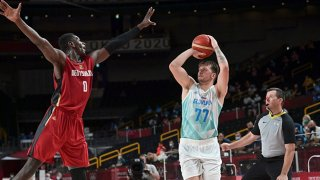 Slovenia's Luka Doncic takes a shot past Germany's Isaac Bonga (L) in the men's quarterfinal basketball match between Slovenia and Germany during the Tokyo 2020 Olympic Games at the Saitama Super Arena in Saitama on Aug. 3, 2021.