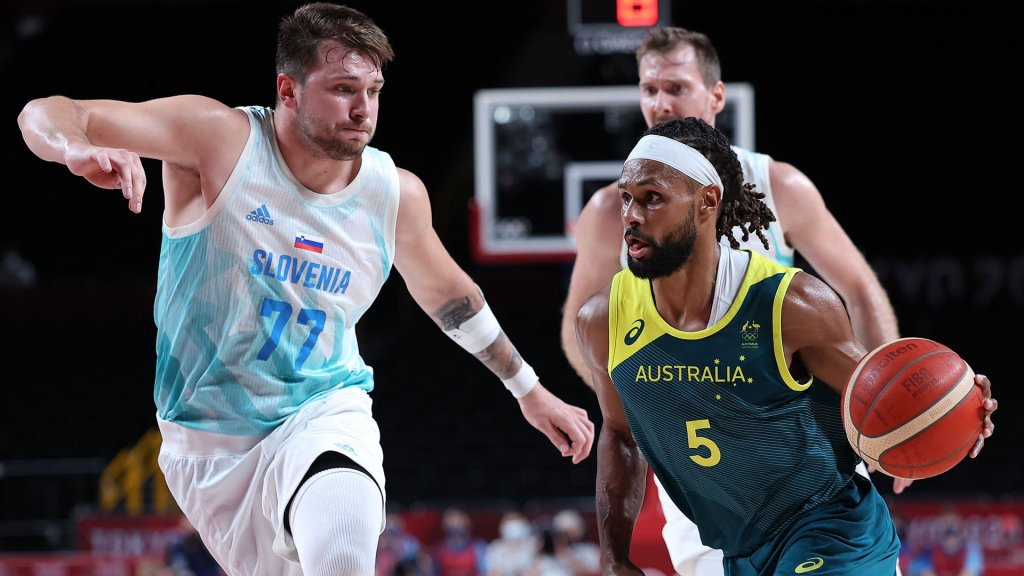Patty Mills dribbles the ball past Slovenia's Luka Doncic.