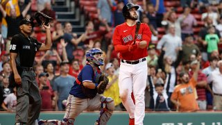 As catcher Jose Trevino #23 of the Texas Rangers and umpire Jeremie Rehak #35 look on, Travis Shaw #23 of the Boston Red Sox watches his game winning grand slam home run during the 11th inning at Fenway Park on Aug. 23, 2021 in Boston, Massachusetts.