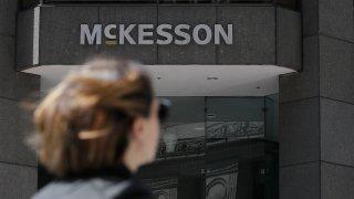Pedestrian passes a McKesson sign