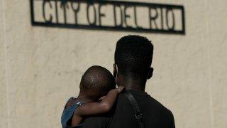 A Haitian migrant carries a boy