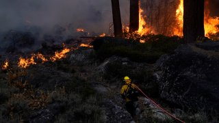 A firefighter carries a water hose toward a spot fire from the Caldor Fire burning along Highway 89 near South Lake Tahoe, Calif., Thursday, Sept. 2, 2021.