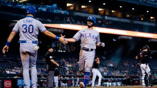 Texas Rangers' Nathaniel Lowe (30) and Nick Solak celebrate after scoring against the Arizona Diamondbacks during the eighth inning of a baseball game Wednesday, Sept. 8, 2021, in Phoenix.