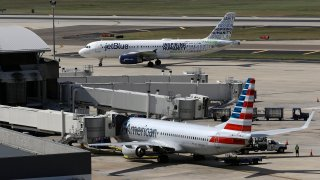 FILE - A JetBlue Airbus A320 taxis to a gate Wednesday, Oct. 26, 2016, after landing as an American Airlines jet is seen parked at its gate at Tampa International Airport in Tampa, Fla. The Justice Department is suing to stop American Airlines and JetBlue from coordinating their flights in the Northeast. Government antitrust lawyers said Tuesday, Sept. 21, 2021, that the deal between the two airlines will reduce competition and lead to higher fares.