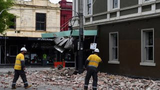 Rescue workers examine a damaged building in the popular shopping Chapel Street in Melbourne on September 22, 2021, after a 5.8-magnitude earthquake.
