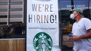 A 'We're Hiring!' sign is posted at a Starbucks on August 06, 2021 in Los Angeles, California. The U.S. economy added over 900,000 jobs in July, the biggest monthly gain since August of last year.