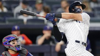 Joey Gallo #13 of the New York Yankees hits a solo home run during the sixth inning against the Texas Rangers at Yankee Stadium on Sept. 21, 2021 in the Bronx borough of New York City.