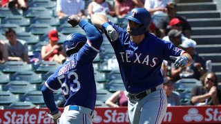 DJ Peters #38 of the Texas Rangers celebrates his three-run home run with Adolis Garcia #53 during the third inning against the Los Angeles Angels at Angel Stadium of Anaheim on Sept. 5, 2021 in Anaheim, California.