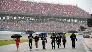 Team members walking through pit row