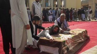 Relatives and residents attend a funeral ceremony for victims of a suicide attack