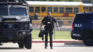 A law enforcement officer walks in the parking lot of Timberview High School after a shooting inside the school in south Arlington, Texas, Wednesday, Oct. 6, 2021.