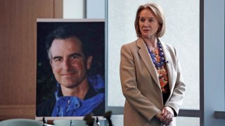 FILE - In this Feb. 21, 2018, file photo, Seattle Mayor Jenny Durkan, former U.S. Attorney for the Western District of Washington, stands near a photo of slain Assistant United States Attorney Thomas Wales in Seattle. Rewards totaling $2.5 million are now being offered for information that helps solve the killing of Wales in Seattle 20 years ago.