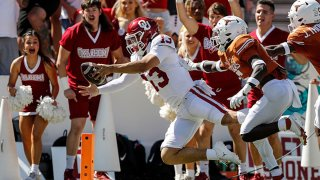 Caleb Williams #13 of the Oklahoma Sooners dives for a touchdown in the first half defended by D'Shawn Jamison #5 of the Texas Longhorns during the 2021 AT&T Red River Showdown at Cotton Bowl on Oct., 2021 in Dallas, Texas.