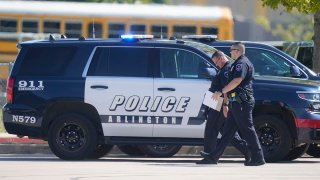 Law enforcement officers walk in the parking lot of Timberview High School after a shooting inside the school located in south Arlington, Texas, Oct. 6, 2021.