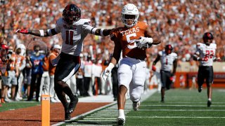 Bijan Robinson #5 of the Texas Longhorns scores a receiving touchdown while defended by Eric Monroe #11 of the Texas Tech Red Raiders in the first quarter at Darrell K Royal-Texas Memorial Stadium on Sept. 25, 2021 in Austin, Texas.
