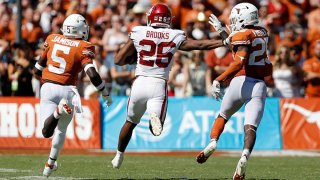 Kennedy Brooks #26 of the Oklahoma Sooners gives a stiff arm to B.J. Foster #25 of the Texas Longhorns in the third quarter during the 2021 AT&T Red River Showdown at Cotton Bowl on Oct. 9, 2021 in Dallas, Texas.