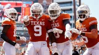 Josh Thompson #9 of the Texas Longhorns celebrates with teammates after an interception return for a touchdown in the second quarter against the Texas Tech Red Raiders at Darrell K Royal-Texas Memorial Stadium on Sept. 25, 2021 in Austin, Texas.