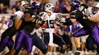 Brigham Young quarterback Max Hall (15) being swarmed by TCU defense during the game between the Brigham Young Cougars and the TCU Horned Frogs. TCU led BYU 23-0 at half time at TCU's Amon Carter Stadium, Fort Worth, Texas.