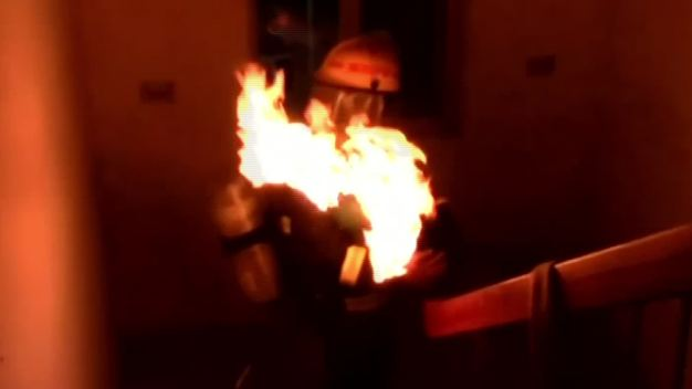 Firefighter Carries Burning Gas Tank from Building