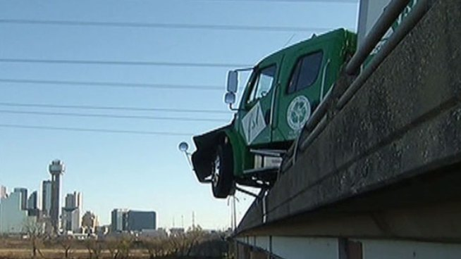 The cab of a big rig was left dangling over the edge of the Interstate 30/Trinity River bridge Thursday morning after a crash involving two freight trucks and an SUV.
