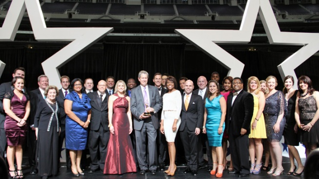 NBC 5 President/General Manager Tom Ehlmann (center in purple tie) holds the Station Excellence Emmy at the 2012 Lone Star Emmy Gala at Cowboys Stadium along with several NBC 5 KXAS-TV staffers.