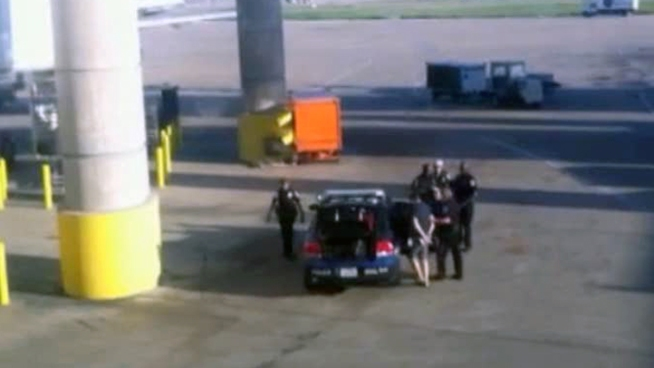 An airline passenger who was escorted off a US Airways flight after someone called in a phony bomb threat was later arrested in North Texas on unrelated outstanding warrants.