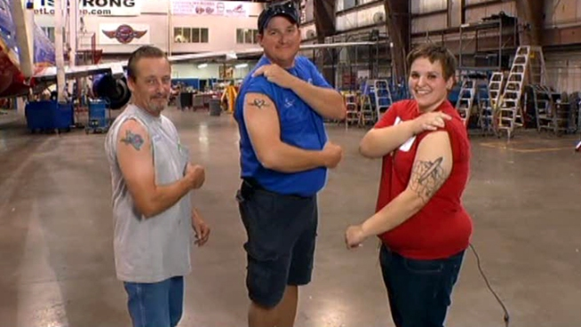 Three Southwest Airlines employees wear their company love on their arms.