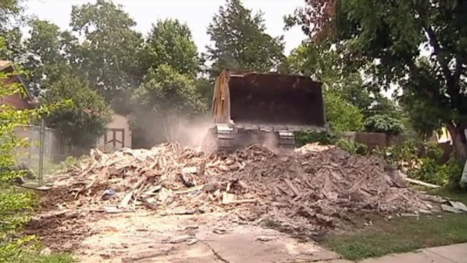 Diane and Jesse Wilmore's home was destroyed by two trailers tossed during April's twister in Dallas. Friday what was left of their home was torn down to make way for new construction.